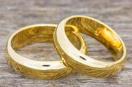 Stock Photo of wedding rings on a wooden floor