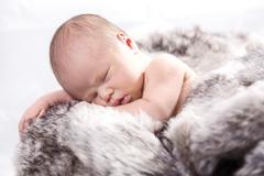 Stock Photo of Baby on fur in wooden crate