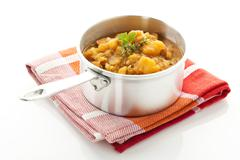 Potato goulash with sausage in saucepan, close up - stock photo