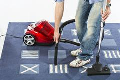 Mature man cleaning carpet with vaccuum cleaner - stock photo