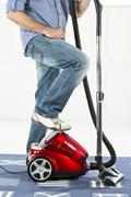 Mature man standing with vaccuum cleaner - stock photo