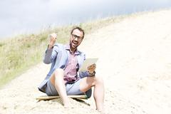 Stock Photo of Germany, Bavaria, Portrait of businessman sitting on sand with digital tablet,
