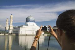 Malaysia, Borneo, Young woman taking photo of City Mosque in Kota Kinabalu - stock photo