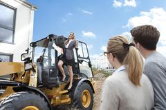 Germany, Neuss, Estate agent driving on wheeled loader on construction site, - stock photo