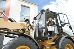 Germany, Neuss, Real estate agent driving wheeled loader on construction site - stock photo
