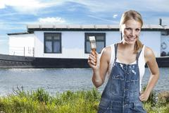 Netherlands, Roermond, Young woman with paintbrush in front of house, smiling, Stock Photos