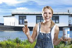 Netherlands, Roermond, Young woman with paintbrush and bucket in front of house, Stock Photos