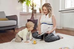 Germany, Bonn, Pregnant mother reading book to son in living room - stock photo