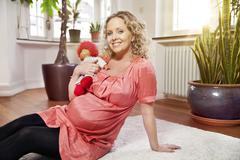 Stock Photo of Germany, Bonn, Portrait of pregnant woman holding doll, smiling