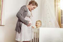 Germany, Bonn, Pregnant mother with son standing near his bed Stock Photos