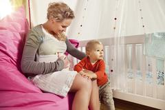 Stock Photo of Germany, Bonn, Pregnant mother explaining her belly to son, smiling