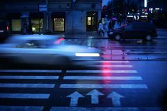 car crossing crosswalk at night, blurred motion. - stock photo