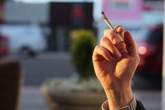 hand with smoking cigarette - stock photo
