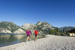 Italy, Mid adult couple jogging by Lake Garda - stock photo