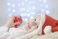 Boy holding christmas bauble, smiling - stock photo