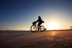 Biker silhouette riding along beach at sunset Stock Photos