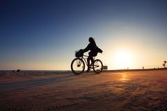 Biker silhouette riding along beach at sunset Stock Photos