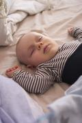 Germany, Hesse, Frankfurt, Baby boy sleeping on bed - stock photo