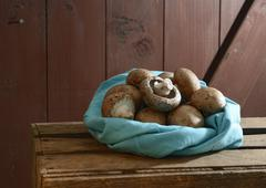 Stock Photo of Organic brown mushrooms in cloth on wooden table