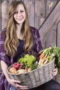Germany, Portrait of teenage girl holding basket with organic vegetables, - stock photo