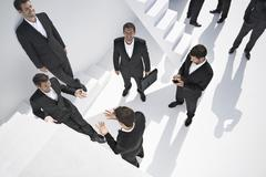 Businessmen doing various activities near stairs - stock photo