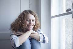 Stock Photo of Germany, Bavaria, Munich, Young woman sitting at window, smiling, portrait
