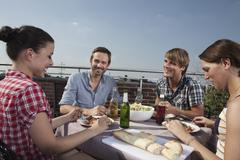 Stock Photo of Germany, Berlin, Men and women at barbecue on roof terrace, smiling