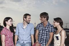 Germany, Berlin, Men and women on roof terrace, smiling Stock Photos