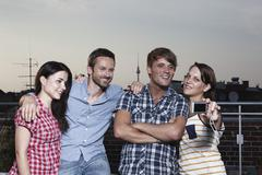 Stock Photo of Germany, Berlin, Group of friends taking self photograph on roof terrace,
