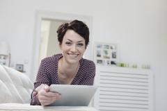 Germany, Bavaria, Munich, Portrait of mid adult woman using digital tablet on Stock Photos