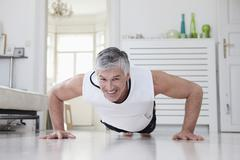 Stock Photo of Germany, Bavaria, Munich, Mature man doing push ups at home, smiling