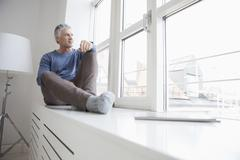 Stock Photo of Germany, Bavaria, Munich, Portrait of mature man sitting at window, looking away