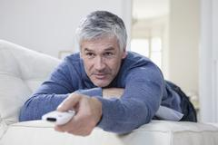 Germany, Bavaria, Munich, Mature man changing channels with remote control Stock Photos