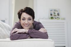 Germany, Bavaria, Munich, Portrait of mid adult woman relaxing on couch, smiling - stock photo