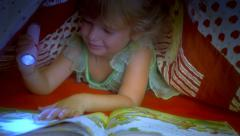 Little girl reading book under covers medium shot Stock Footage