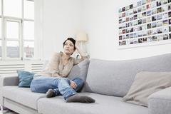 Stock Photo of Germany, Bavaria, Munich, Mid adult woman sitting on couch, looking away