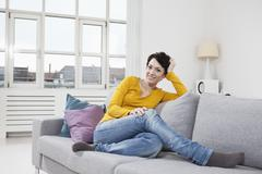 Stock Photo of Germany, Bavaria, Munich, Portrait of mid adult woman sitting on couch, smiling