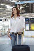 Germany, Cologne, Young woman with luggage at airport - stock photo