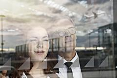 Germany, Cologne, Young woman and mature man looking through window at airport Stock Photos