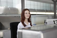 Germany, Cologne, Young woman at ticket counter - stock photo