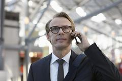 Germany, Cologne, Mature man on phone at airport - stock photo