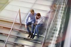 Germany, Cologne, Young woman and mid adult man with tablet at stairs Stock Photos