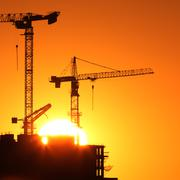 Industrial construction cranes and building silhouettes over sun at sunrise. Stock Photos