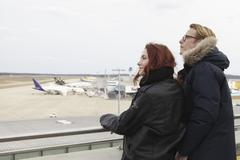 Germany, Cologne, Young woman and mature man looking at airport - stock photo