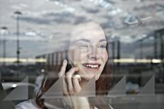Germany, Cologne, Young woman on phone at airport Stock Photos