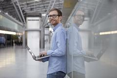 Stock Photo of Germany, Cologne, Mid adult man holding laptop, portriat