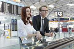Germany, Cologne, Young woman and mature man at airport Stock Photos