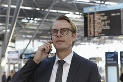 Germany, Cologne, Mature man talking on phone at airport - stock photo
