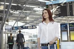 Stock Photo of Germany, Cologne, Young woman with baggage at airport