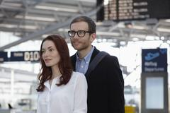 Germany, Cologne, Young woman and mid adult man at airport Stock Photos